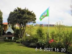 Fotos zeigen das Ferienhaus Kolks Huus Carolinensiel Harlesiel, einfach schöne Ferien mit Ruhe und freiem Blick auf den Innendeich und die Seenotrettung mit Strandkorb auf dem Deich, Gartengrill und Flagge