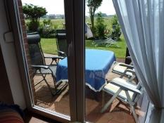 Blick auf die Terrasse mit Sitzgarnitur, Relaxsesseln und Liegestühlen vom Ferienhaus Kolks Huus Carolinensiel Harlesiel