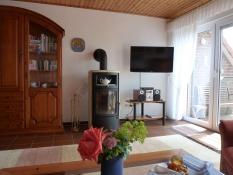 Gepflegtes Wohnzimmer mit Kaminofen und Flachbildfernseher im Ferienhaus Kolks Carolinensiel Harlesiel