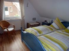 Geräumiges Elternschlafzimmer im Ferienhaus Kolks Carolinensiel Harlesiel mit Bettwäsche und Handtüchern, Kleiderschrank und Kommoden, Spiegel und Tresor