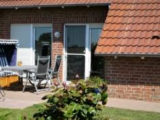 Fotos vom Ferienhaus Kolks Huus in Carolinensiel Harlesiel zeigen mit der windgeschützten Südterrasse mit Strandkorb, Liegesesseln und leichten Aluminium-Stühlen schöne Ferien direkt an der Nordsee für 4 Personen